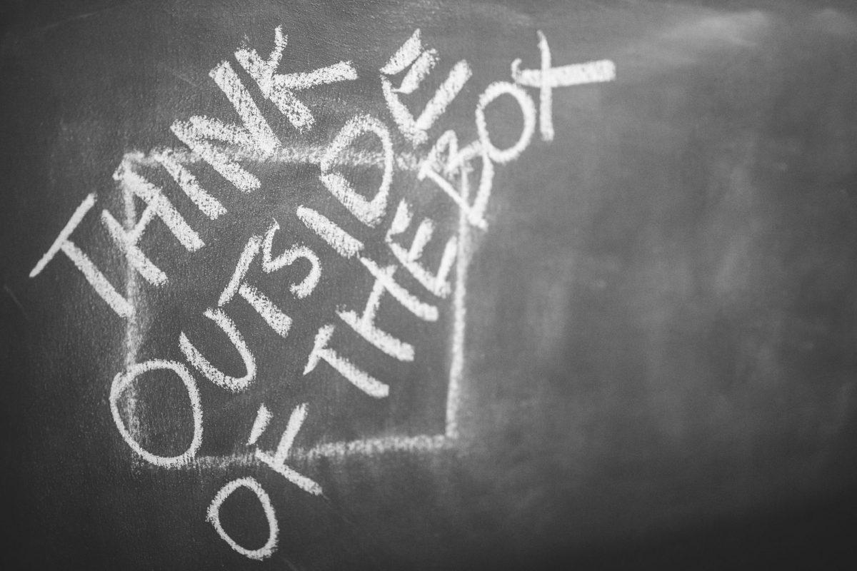 """Think outside of the box"" written on chalkboard"